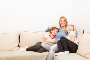 49410537 - young mother and daughters bonding on at home on a couch or sofa